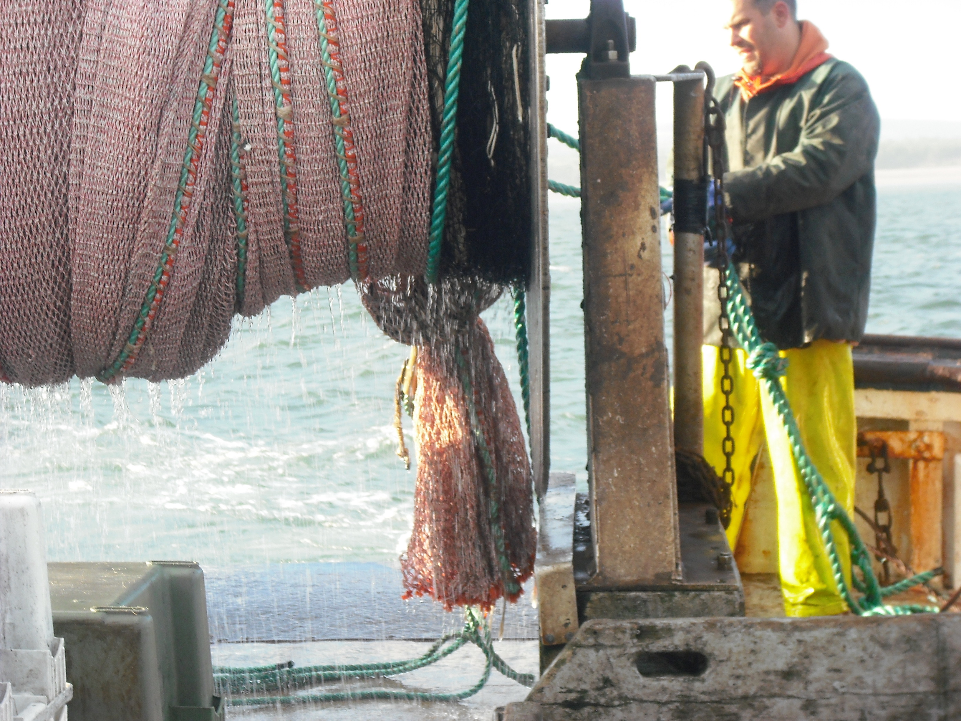 Stern of boat with trawl net on reel and fisherman